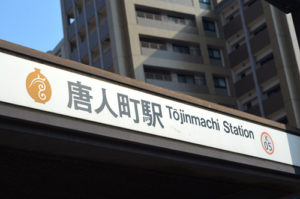 Tojinmachi Station sign at subway entrance.